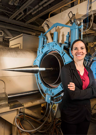 Katya Casper stands in front of wind tunnel