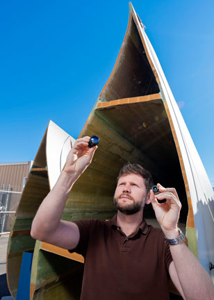 scientist inspects small camera in front of wind turbine