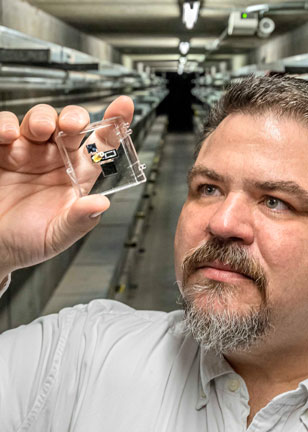 scientist holds up micro gas sensor