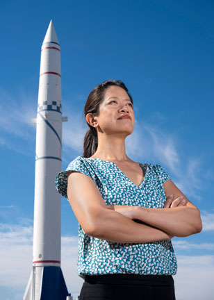 Frances Chance poses in front of missile