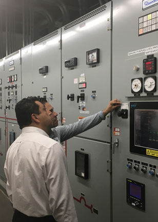 engineers inspect a bank of switchgear