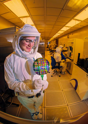 microelectronics technician in HAZMAT suit studies a wafer