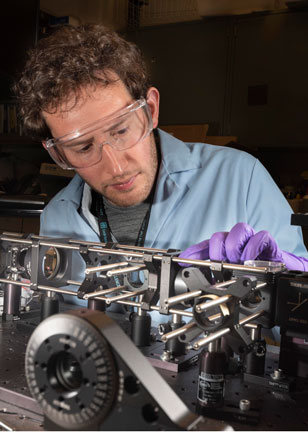 optical scientist works on microsopy equipment
