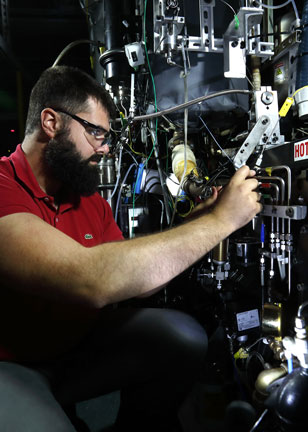 Researcher adjusts engine part in lab