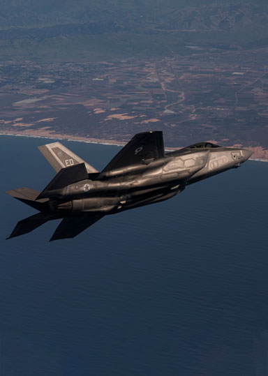F-35A Lightning II jet fighter in flight over coastline